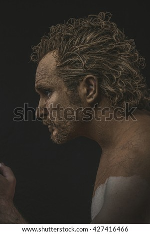 covered with mud all over her naked body on black background man. adventure and risk, competition force - stock photo