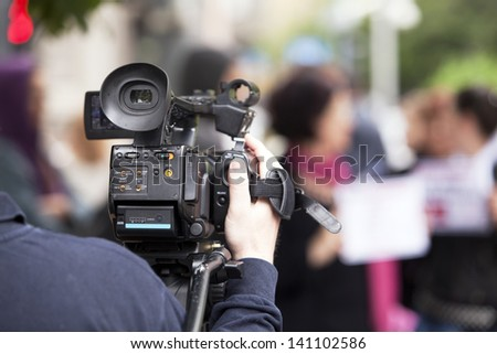 Covering a street protest using video camera - stock photo