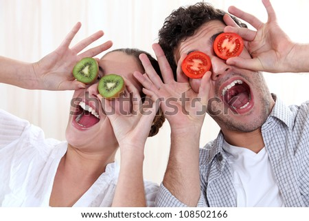Covering his eyes with a couple slices of kiwi and tomato - stock photo