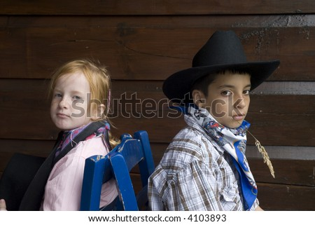 Cow-boy and cow-girl sitting back-wise - stock photo