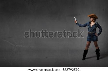 cow girl aiming with gun, dark background - stock photo