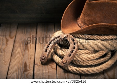 Cowboy. American West rodeo old horseshoe on lariat lasso and roping work gloves with Western horse rider gear with hat and aged leather roper boots on antique wood boars in a ranch barn - stock photo