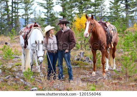 Cowboy and cowgirl in the mountains with their horses - stock photo
