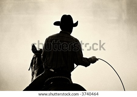 cowboy at the rodeo - shot backlit against big cloud of dust, converted with added grain - stock photo