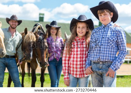 cowboy brother and sister closeup portrait on horseback - stock photo