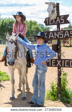 cowboy brother and sister with a signpost - stock photo