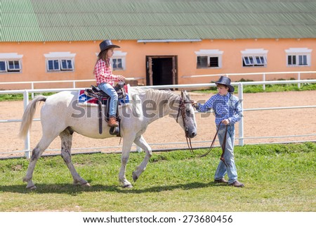 cowboy brother leads the horse of his sister by the reins - stock photo