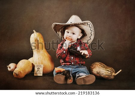 cowboy child in a hat with a gun lying on a floor among the pumpkins - stock photo