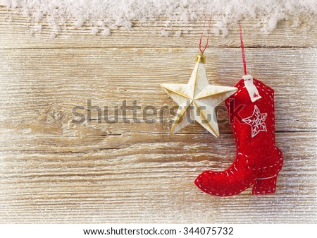 Cowboy christmas background with western toy boot and star on wood texture - stock photo