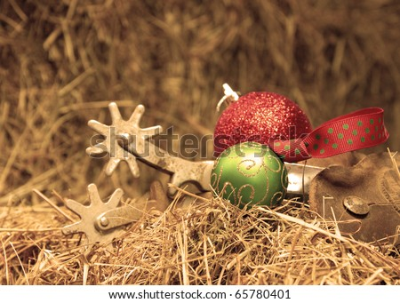 Cowboy Christmas - Christmas ornaments with a set of old rusty spurs on hay in sepia tone - stock photo