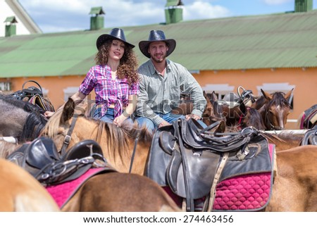 cowboy couple smiling among horses - stock photo