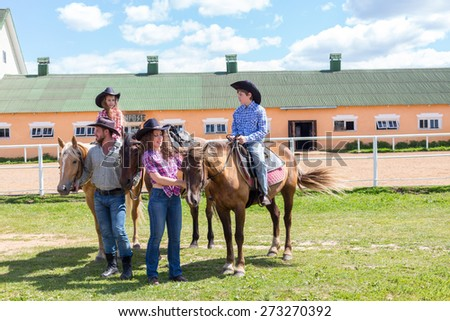 cowboy family of four with horses on grass - stock photo