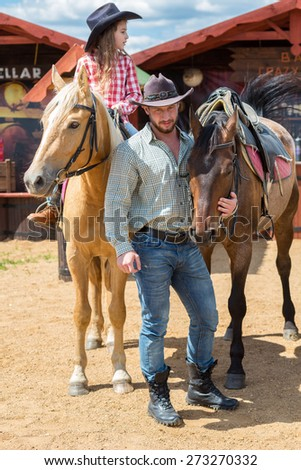 cowboy father and daughter with horses - stock photo