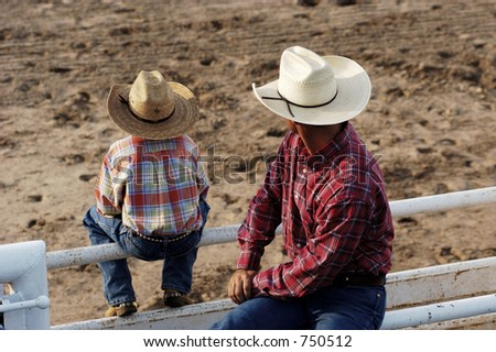 Cowboy father and son watching rodeo action. - stock photo
