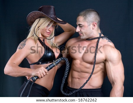 Cowboy girl and boy. Art shot of a pretty model with whip. - stock photo