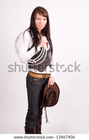 Cowboy girl. Art shot of a pretty model with rope. - stock photo