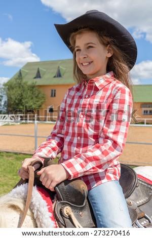 cowboy girl on horseback smiling closeup - stock photo