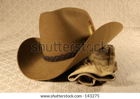Cowboy hat and leather work gloves. - stock photo