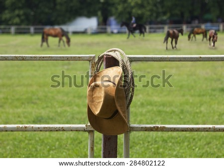 Cowboy hat and rope on fence American Horse ranch - stock photo