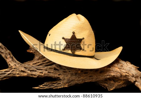 Cowboy hat and sheriff's badge isolated over black - stock photo