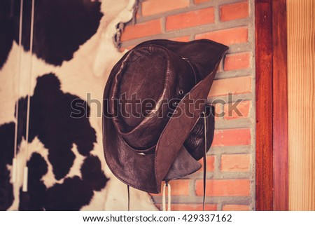 Cowboy hat hanging on brick wall. - stock photo