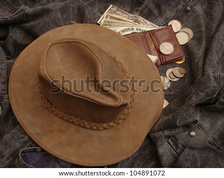 Cowboy Hat over Gun Handle and Wallet Overflowing with Large Paper Money, Silver and Gold Coins - stock photo
