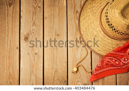 Cowboy hat with red bandanna on wooden rustic background. View from above - stock photo