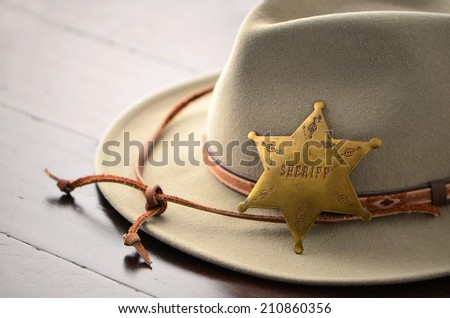 Cowboy hat with Sheriff badge on wooden background in horizontal format with selective focus - stock photo