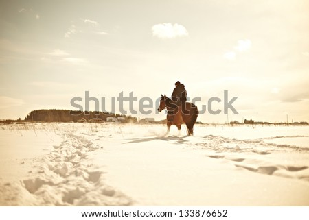 Cowboy In Snowy Winter Desert, the image on the background of the solar sky - stock photo