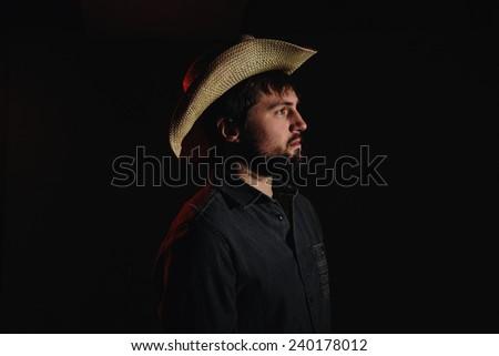 Cowboy in Studio Lighting body turned towards light - stock photo