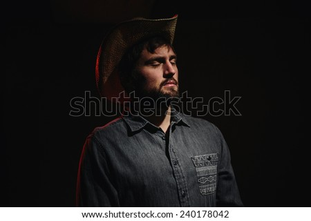 Cowboy in Studio Lighting looking at light eyes closed - stock photo