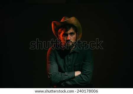 Cowboy in Studio Lighting serious face leaning over chair - stock photo