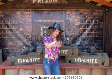 cowboy lady gesticulates on backgroud of boxes of dynamite - stock photo