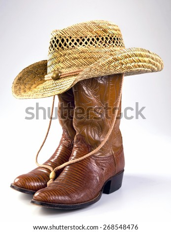 Cowboy lizard skin boots and straw hat. - stock photo