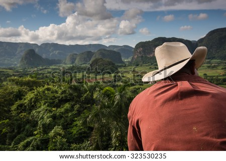Cowboy looking over Vinales Valley landscape with mogotes in Cuba