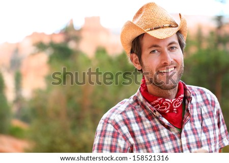 Cowboy man smiling happy wearing hat in rural USA. Male model in american western countryside landscape nature on ranch or farm, Utah, USA. - stock photo