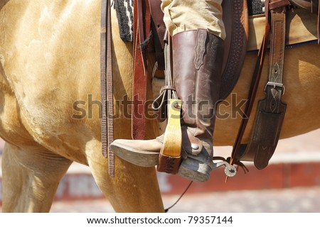 Cowboy on a horse riding in a saddle with spurs. - stock photo