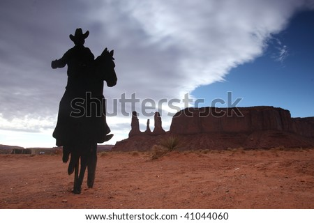Cowboy on a Horse Silhouette With Three Sisters Monument in the Background - stock photo