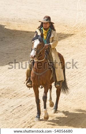 Cowboy riding his horse into town - stock photo