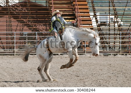 Cowboy riding in bareback competition in rodeo.