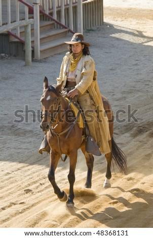 Cowboy riding into town - stock photo