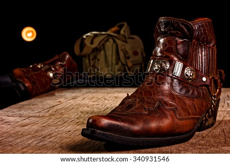 Cowboy shoes and bag carelessly thrown on the wooden floor