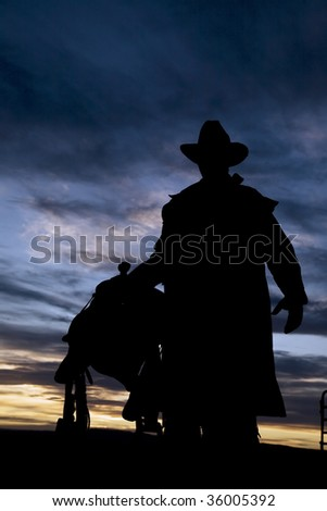 Cowboy silhouette carrying a saddle - stock photo