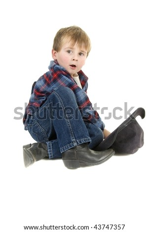 Cowboy toddler sits on floor with hat and leather boots - stock photo