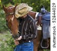 Cowboy with his horse - stock photo