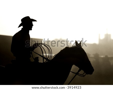 cowboy with horse and lasso, a dusty backlit silhouette. converted with added grain, shot in small town Wyoming - stock photo