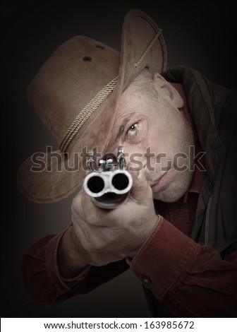 Cowboy with shotgun aiming at you. Gun control concept.  - stock photo