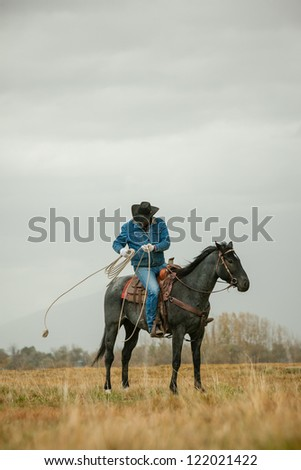 Cowboy wrapping up lasso after use - stock photo