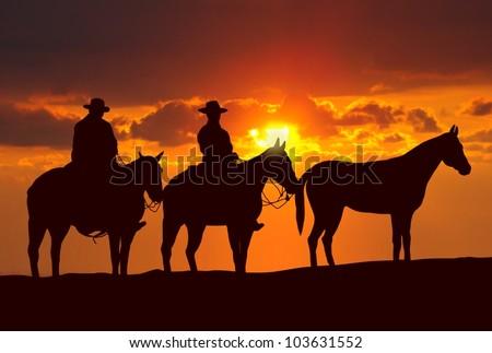 cowboys and horses under sunset - stock photo