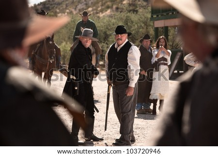 Cowboys draw weapons in an old American west gunfight - stock photo